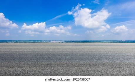 Countryside asphalt road and horizon under blue sky.