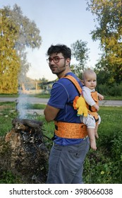Countryside camping! Young father are carrying a little baby in ergo backpack kangaroo.