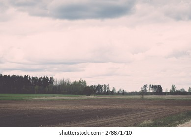 countryside fields in early spring with clouds and farmland - retro vintage grainy film look