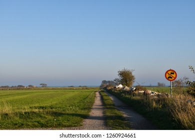 Countryside gravel road with a traffic sign at the swedish island Oland