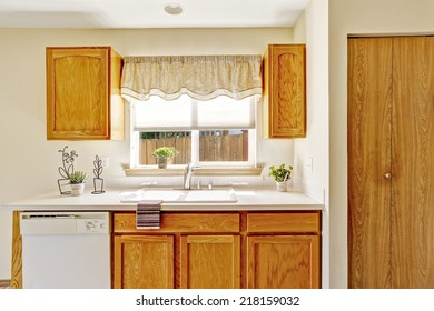 Countryside house interior. Kitchen room with wooden storage cabinets and window view