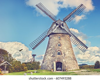 Countryside landscape with old windmill among hills and colorful clouds , Europe
