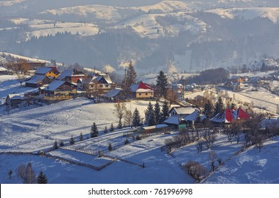 Countryside landscape with traditional Romanian village in the valleys of Bucegi mountains on a sunny cold winter morning in Pestera, Brasov county, Transylvania region, Romania.
