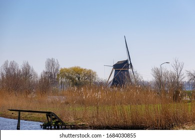 Countryside landscape view with beautiful traditional Dutch windmill under blue sky, Sunny day with green grass on the field dried common reed along the Gein river near Abcoude, Netherlands.