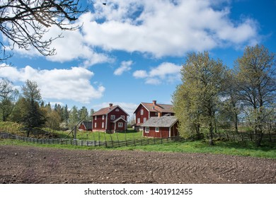 Countryside living idyll - Rural Swedish idyllic landscape in springtime - Red painted houses and plowed fields in the travel destination Asens By in Smaland Sweden.