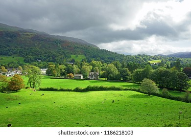 The countryside near Grasmere in late summer/early Autumn after a clearing storm with sunlight breaking through the rain clouds and sheep grazing in the meadow, The Lake District, Cumbria, UK