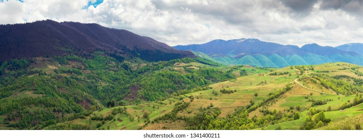 countryside of panorama in springtime. rural fields on hillside, mountain ridge in the distance. overcast sky