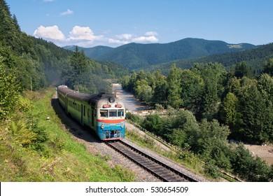The countryside and the railroad in the Ukrainian Carpathians. Diesel passenger train arrives at the station Tatariv (Tatarov), Ivano-Frankivsk region, Yaremche district, Ukraine. D1 diesel train.