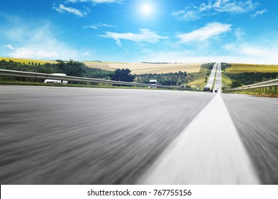 A countryside road in motion with different cars against a blue sky with white clouds