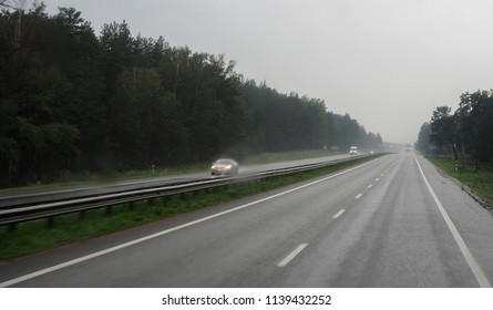Countryside road and several cars in rainy overcast day