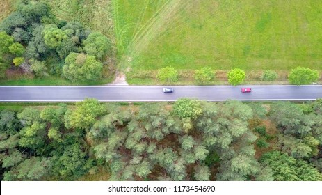 Countryside road, surrounded by lush green nature - Top down aerial image