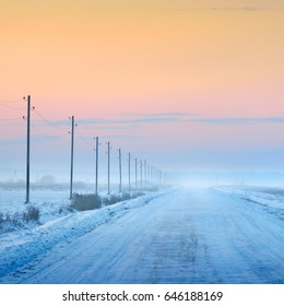Countryside road with telegraph poles on a winter day under snow at sunset