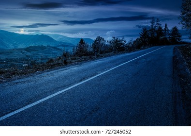 countryside road through mountains at night in full moon light. lovely autumnal scenery