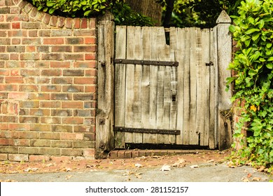 Countryside scene. Rustic old wooden gate in brick wall.