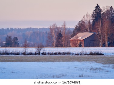 Countryside scenery with old barn and snow on the field. Very calm and peaceful atmosphere of cold day in winter.