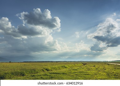 Countryside scenery with vast green pastures and sun rays passing through stormy clouds in Transylvania region, Romania.