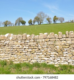 Countryside View of an Old Stone Wall and Farmland Beyond