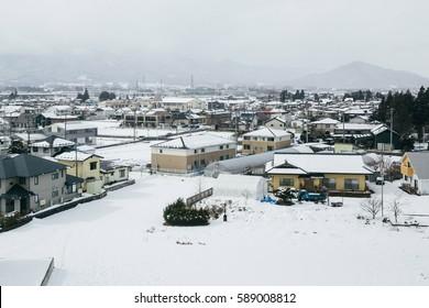 Countryside village along railway covered by snow, Tohoku, Japan.