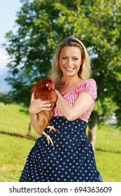 Countrywoman with traditional costume is holding a chicken