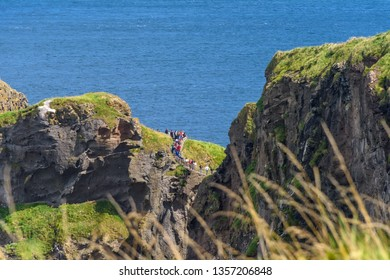 County Antrim, Northern Ireland - August 10, 2018:  Tourists take the long walk across the Carrick-a-Rede Rope Bridge near the Giants Causeway in Northern Ireland.