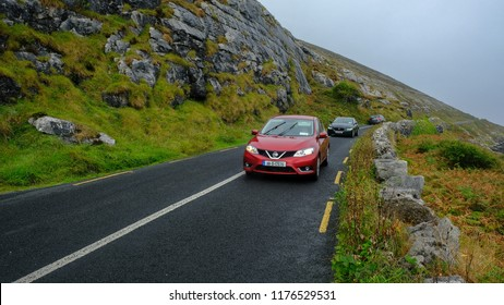 County Clare, Ireland; 19/08/2018; A red car driven from Cliff of Moher using Causeway Road to Galway, Ireland.