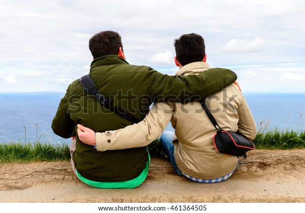 COUNTY CLARE, IRELAND - JULY 13, 2016: Friends together at the Cliffs of Moher (Aillte an Mhothair), Burren region in County Clare, Ireland. Great touristic attraction