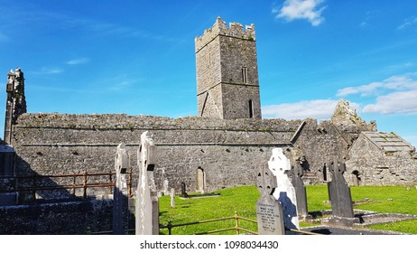 County Clare, Ireland - May 23 2018: Burial graveyard over looked by Old ruins from Clare Abbey Ireland.