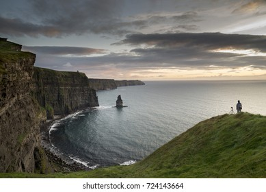 COUNTY CLARE, IRELAND - SEPTEMBER 29, 2017: A lonely photographer with a tripod watching colorful sunset over Cliffs of Moher.