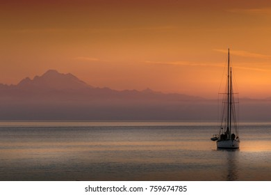 COUPEVILLE, WASHINGTON - SEPTEMBER 27, 2017: Dawn photo of a sailboat at anchor in Puget Sound with Mt Baker in the background.