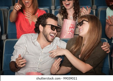 Couple with 3D glasses in theater laughing together