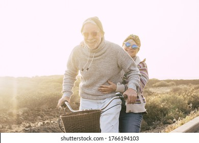 Couple of active cheerful and happy senior retired people enjoy together riding a bike in outdoor leisure activity with sun in backlight - concept of old age and fun joyful with no limit
