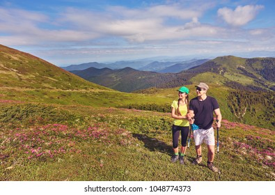 Couple - active hikers hiking enjoying view looking at mountain forest landscape in Yosemite National Park, California, USA. Happy multiracial outdoors couple, young Asian woman and Caucasian man.