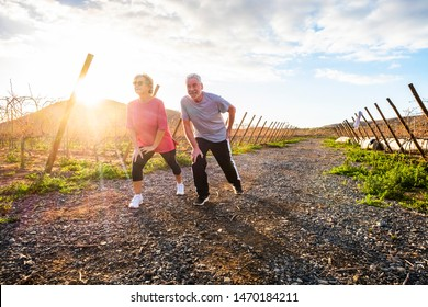 Couple of active senior do stretching and sport activity outdoor enjoying the healthy lifestyle - sunset in background and country side scenic landscape