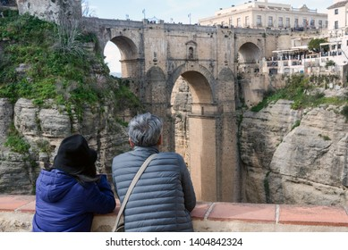 The couple admires the sights of the Spanish city of Ronda. The famous Puente Nuevo is a new bridge over the Guadalevn River over the El Tajo Gorge. Business card Rhonda. Andalusia.