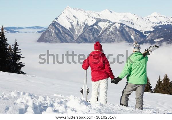 Couple Admiring Mountain View Whilst On Ski Holiday In Mountains