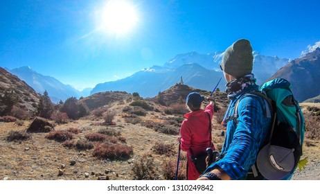 A couple admiring the views on the Annapurna Circuit Trek, Himalayas, Nepal. Annapurna chain in the back, covered with snow. White Stupa in front of them. Girl pointing to the peaks. Boy holding gopro