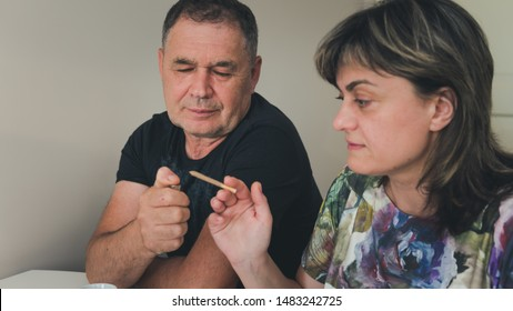 The couple of adult persons are smoking medical marijuana joint. Smoking hemp indoors. Cannabis is a concept of herbal medicine