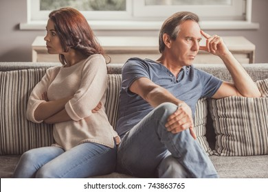 Couple of adults offended at each other are sitting back to back on couch at home