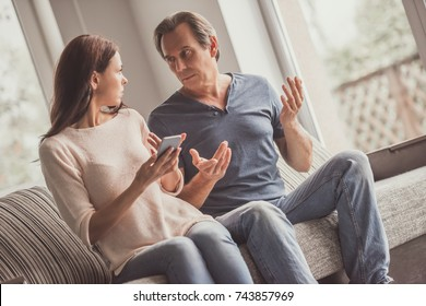Couple of adults are using a smart phone and talking while sitting on couch at home