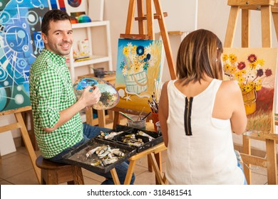 Couple of adults working on a painting at an art school and smiling