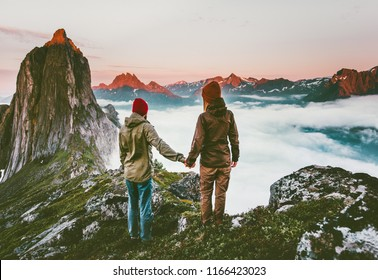 Couple adventurers hands holding  traveling in Norway mountains healthy lifestyle concept active vacations outdoor hiking Segla together enjoying sunset landscape