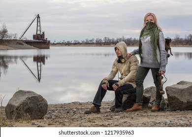 Couple of adventurers: man in hood and gas mask on his neck and women in neckerchief scarf on face, telescope in hand and a backpack. HDR image