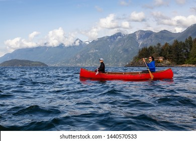 Couple adventurous female friends on a red canoe are paddling in the Howe Sound during a cloudy and sunny evening. Taken near Horseshoe Bay, West of Vancouver, BC, Canada.