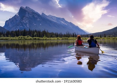 Couple adventurous friends are canoeing in a lake surrounded by the Canadian Mountains. Colorful Sunrise Sky Art Render. Taken in Vermilion Lakes, Banff, Alberta, Canada.