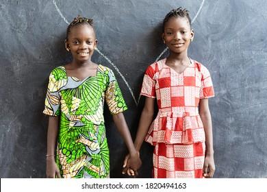 Ein paar afrikanische Kinder, die in Schulgebäuden mit Händen sitzen