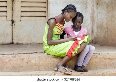 Couple of African Schoolgirls Learning Repeating their lessons outside of a classroom. Older girl showing younger child how to do their homework. Africa Education Symbol.