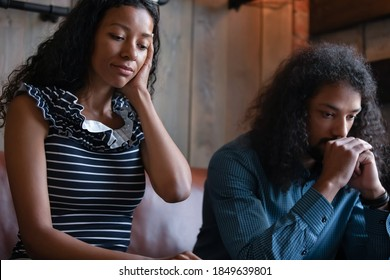 Couple after argument. Sad depressed millennial mixed race family husband and wife sitting on sofa feeling bad frustrated falling in heavy thoughts keeping silence avoid talking ignoring one another