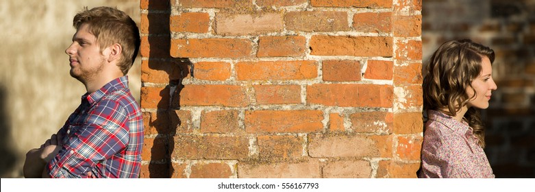 Couple after an argument stands on different sides of the wall. Horizontal photo banner for website header design with copy space for text