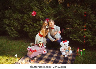 Couple after marriage proposal being on date in the park with picnic organized on plaid. Decorations in the forest for romantic time