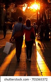 Couple after shopping walking at Parisian pedestrian street in golden sunset light. Back view. Paris (France).  High contrasting backlight.